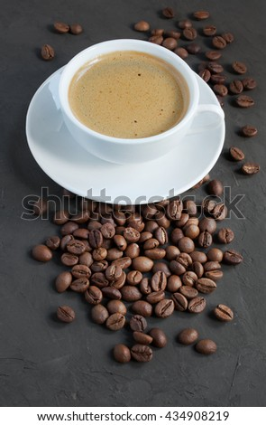 Ã?up of espresso and coffee beans on a dark background