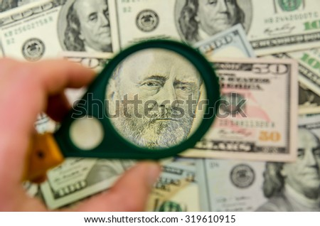 50 US dollars under a magnifying glass. close-up - stock photo
