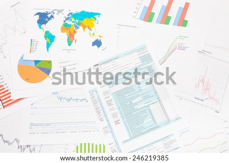1040 US Tax Form with financial graphs on table - stock photo