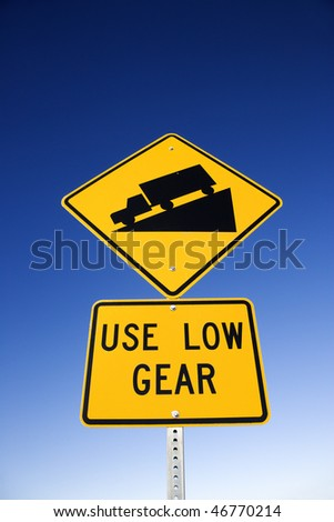 'Use low gear' and steep grade warning signs. Vertical shot.