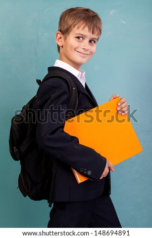 ��¡ute schoolboy is holding an orange book against school blackboard - stock photo