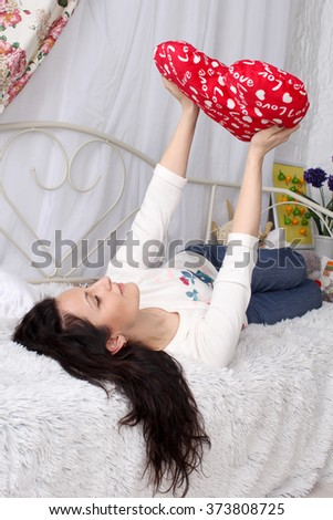 Valentine's Day. Beautiful girl lying on the bed. In the hands of the pillow heart red. She looks at the heart and dreams of love.  - stock photo