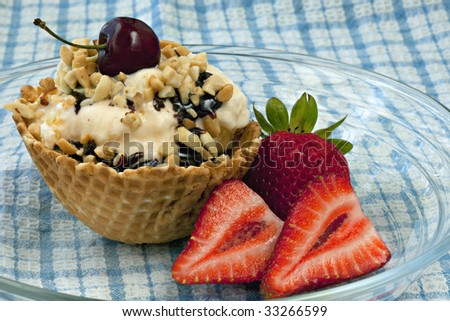 Vanilla Ice Cream Sundae in an edible waffle bowl with chocolate syrup, nuts, strawberries on the side, and a cherry on top sitting on clear plate on blue and white checked tablecloth - stock photo