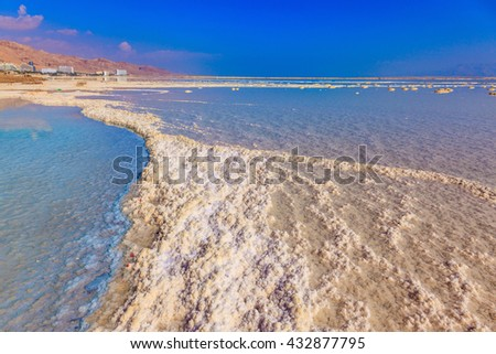 Vaporized salt form whimsical patterns on the water surface. Dead Sea off the coast of Israel - stock photo