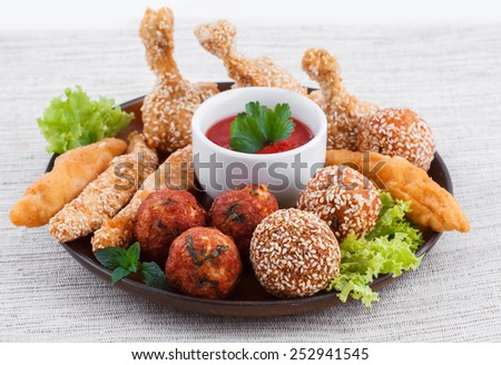Various fried chicken appetizers with tomato dip - stock photo