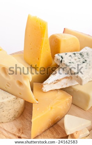 Various types of cheese on a wooden cutting board - stock photo
