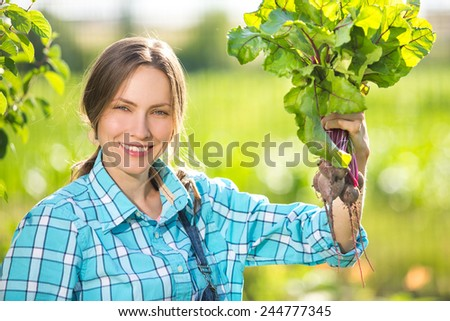 Vegetable garden - lovely gardener with bunch of beetroots. focus on face - stock photo