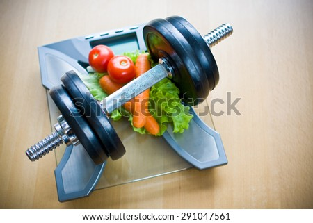 Vegetables and dumbbells on bathroom scale - stock photo