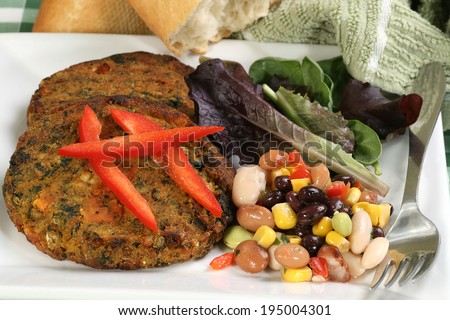 vegetarian lentil and spinach burgers wit four bean salad                               - stock photo