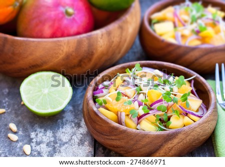vegetarian salad with mango oranges and red onion on the wooden plate - stock photo