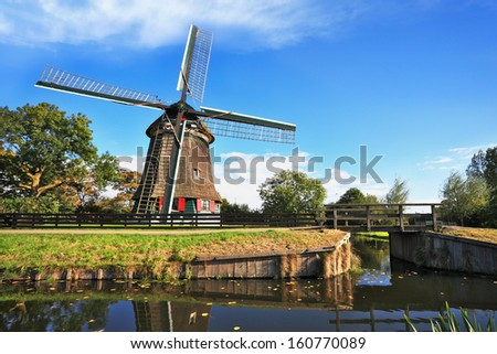 Verdant grove, quiet stream and a symbol of the country - Windmills. Rural landscape in the Netherlands