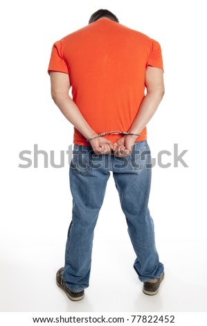 vertical of man in handcuffs on his wrists, head hung in shame, seen from behind isolated on white - stock photo