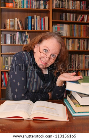 vertical orientation of a middle-aged woman in business attire with shallow depth of field, smiling and happy at a desk of books in a library / The Lifelong Learner - stock photo