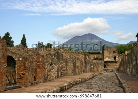 """Via Di Mercurio"" with tower 11 at the end of the street with a view of Mount Vesuvius in the background in the archaeological site of Pompeii, Italy"