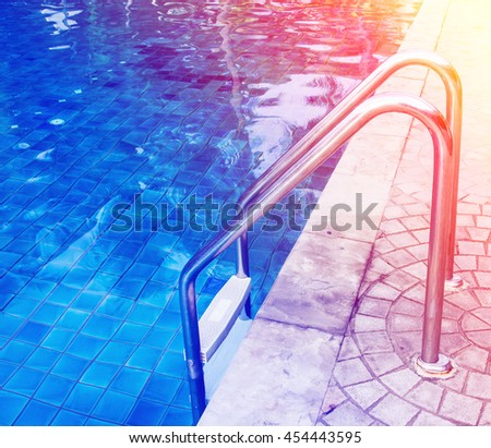 view clear blue swimming pool with steel ladder. - stock photo