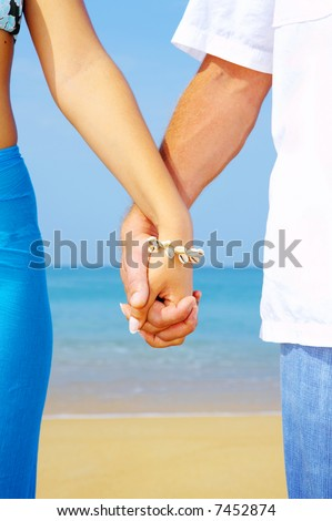view of a young couple holding hands on the beach - stock photo