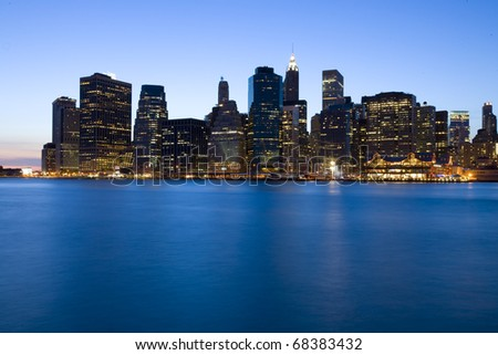 view of Manhattan skyline at dusk over Hudson River with skyscrapers