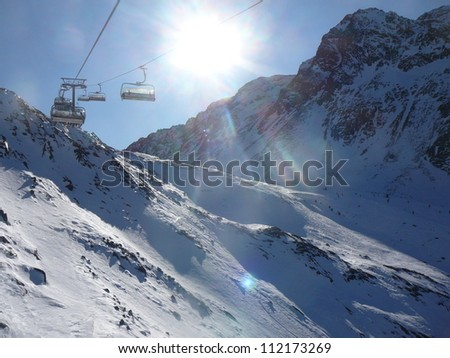 view to empty chair lift and snowcovered Alps