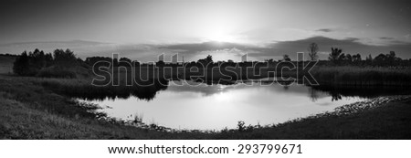 Village on banks of river and beautiful rays of sun in sky. Panorama. Mirror reflection in water. Black and white photo - stock photo