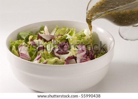 Vinaigrette dressing pouring over fresh salad bowl. - stock photo