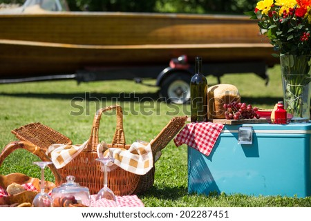 vintage A picnic at the lake house with a vintage boat in the background - stock photo