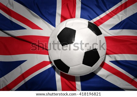 vintage black and white football ball on the national flag of great britain - stock photo