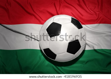 vintage black and white football ball on the national flag of hungary - stock photo