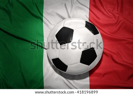 vintage black and white football ball on the national flag of italy - stock photo