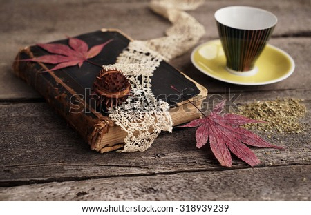 Vintage composition of old book and autumn leaves and cup - stock photo