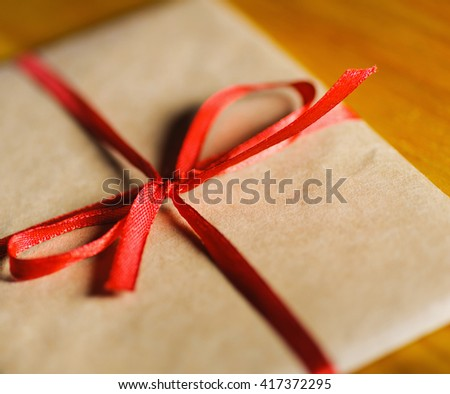 vintage envelope of kraft paper with red ribbon. Close-up selective soft focus technique - stock photo