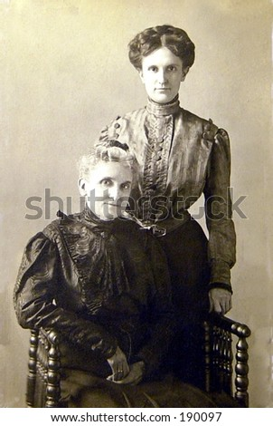 1905 vintage mother & daughter.  Note crisp detail taffeta dresses & wasp waist on daughter. - stock photo