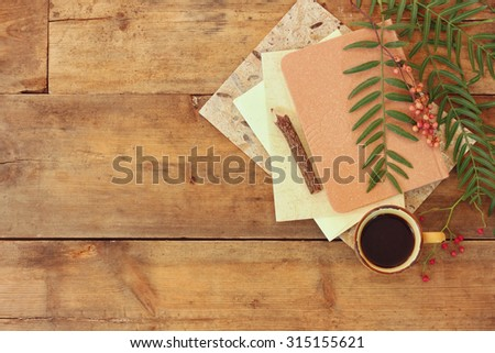 vintage notebook, old paper and wooden pencil next to cup of coffee over wooden table. ready for mockup  - stock photo