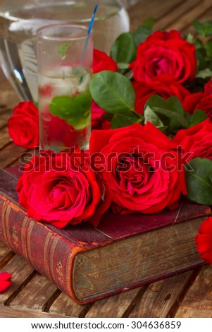 vintage old book  on table with red roses and long drink - stock photo