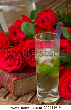 vintage old book  on table with roses and long drink - stock photo