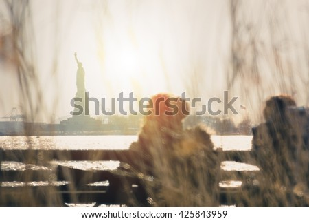 (Vintage) 2 people sitting down chilling against Statue of Liberty in the background. This picture of Statue of Liberty is in New York Harbor.  New York Harbor is in New York City, New York, USA - stock photo