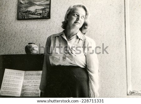 Vintage photo of woman with a piano and music, forties - stock photo