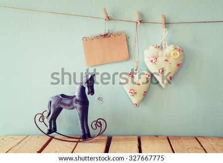 vintage rocking horse next to fabric hearts and empty card for adding text hanging on the rope on wooden floor. retro filtered image - stock photo