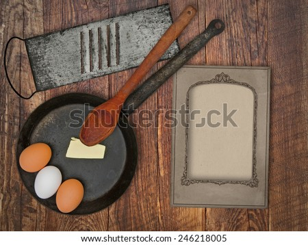 vintage utensils set, skillet,spoon,grater, eggs,butter, space for your text on a blank menu card - stock photo