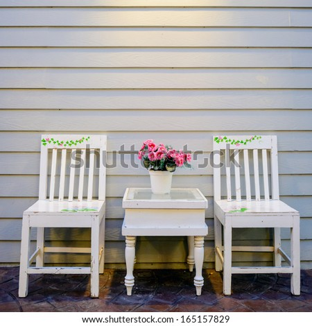 Vintage white wooden wall and chair  in The light of lamp - stock photo