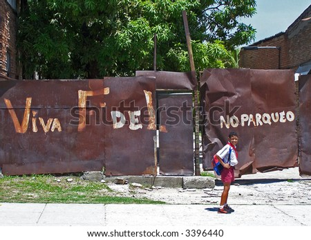 """Viva, Fidel!"" - painted on a wall propaganda and a schoolboy. Havana. Cuba - stock photo"