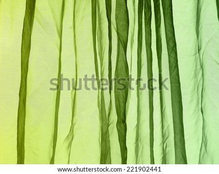 Voile curtain fading colors lime to green background    - stock photo