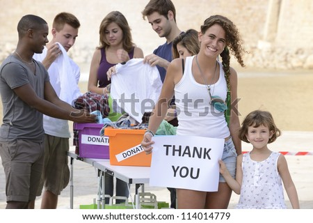 volunteer group saying thank you for clothing donation - stock photo