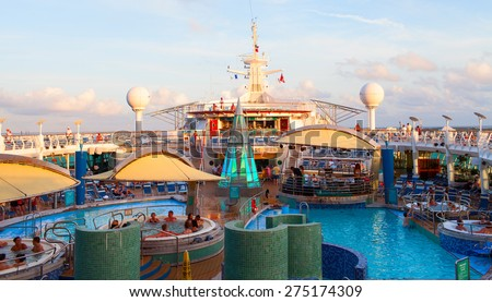 """""""VOYAGER OF THE SEAS"""", ROYAL CARIBBEAN INTERNATIONAL - JANUARY 10, 2012: Open pool deck of the large cruise ship during sunset time. - stock photo"""