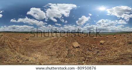 360 VR panorama  Beautiful summer sky over freshly harvested wheat field, littered with small cubical hay bales  NOTE: its not banding in the sky, those are sun rays clearly visible in VR - stock photo