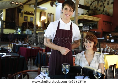 waiter and happy costumer at the restaurant with copy space