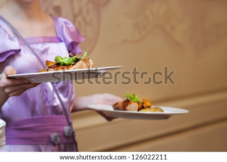 Waiter carrying two plate with meat and baked potato - stock photo