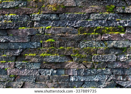 Wall made of natural stones with the growing moss  - stock photo