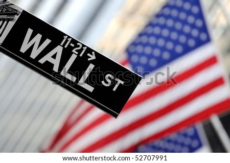"""Wall Street"" sign in focus, pointing down, with American flags blurred in the background, shot in the heart of the business world in Manhattan. - stock photo"