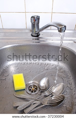 wash the forks and spoons - stock photo