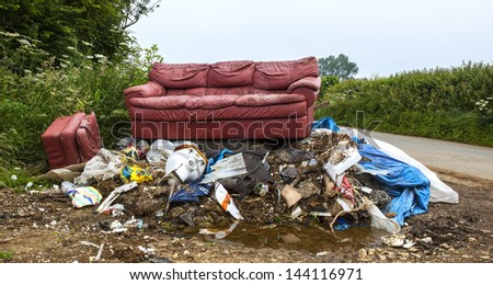 Waste dumped in the countryside, an illegal social issue, fly tipping causing environmental pollution - stock photo